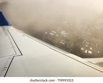 Aerial view of city below while flying into clouds