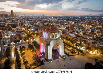 Aerial view of city centre showing architectural landmark Monument to the Revolution (Spanish: Monumento a la Revolucion) located in Plaza de la Republica at dusk in Mexico City, Mexico.