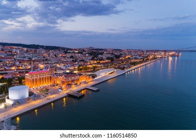 Aerial view of the city of Lisbon and the 25 of April Bridge on the background at dusk; Concept for travel in Portugal and visit Lisbon