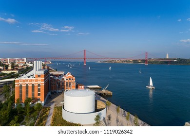 Aerial view of the city of Lisbon with sail boats on the Tagus River and the 25 of April Bridge on the background; Concept for travel in Portugal and visit Lisbon
