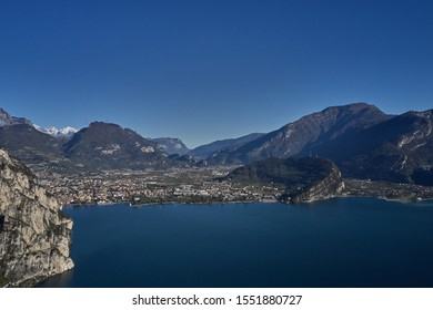 Aerial view of the city of Riva del Garda, Italy. Panoramic view of Lake Garda in the foreground, the city is surrounded by rocks and alpine mountains. Autumn season.