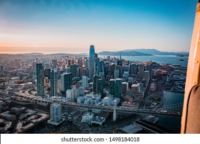 An aerial view of the City of San Francisco and the bay bridge from a helicopter during sunset.