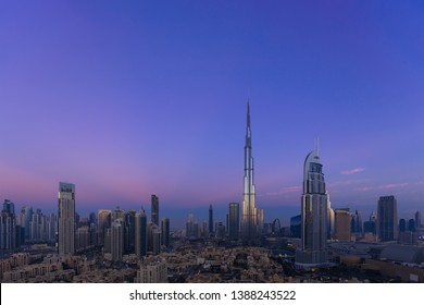 Aerial view of city skyline and cityscape at sunrise in Dubai