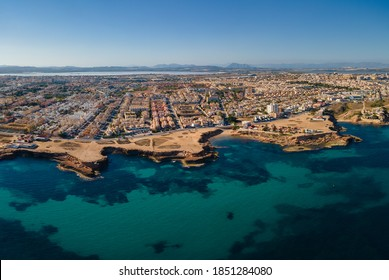 Aerial view of the city of Torrevieja on a sunny autumn afternoon with sunshine. In the foreground are rocky bays and in the background the salt lagoon.