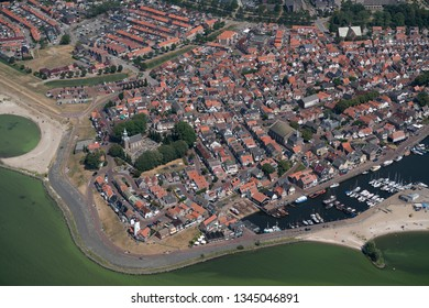 Aerial view of the city of Urk, an old fishermans town in Flevoland, Holland. It has a harbour with boats, lighthouse and an old church.