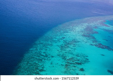 Aerial view of the clear blue Indian Ocean from seaplane while island hopping in the Maldives.