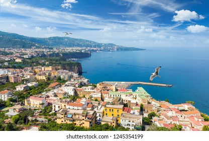 Aerial view of cliff coastline Sorrento and Gulf of Naples in Italy. Sunny summer day with blue sky, clear sea and green mountains of Sorrento Peninsula.