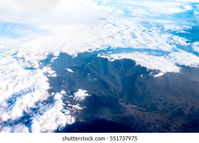 Aerial view of cloud and sky from airplane window looking down to land ,Nature background.