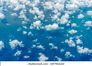 Aerial view of clouds and blue sky over ocean, cloudscape top view from airplane