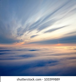 Aerial view of a cloudy sunset while flying above the clouds.