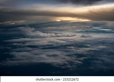 Aerial view of a cloudy sunset while flying above the clouds