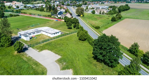 Aerial view of the clubhouse of a regional football club on the outskirts of the city next to a big street, football field in the background, near Wolfsburg