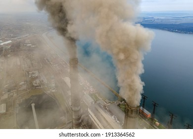 Aerial view of coal power plant high pipes with black smoke moving up polluting atmosphere.