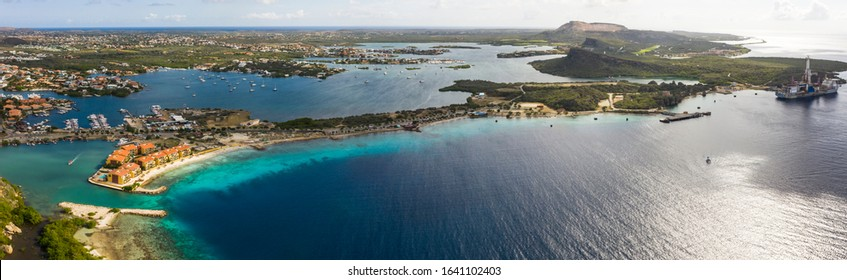 Aerial view of coast of Curaçao in the Caribbean Sea with turquoise water, cliff, beach and beautiful coral reef over Caracas Bay