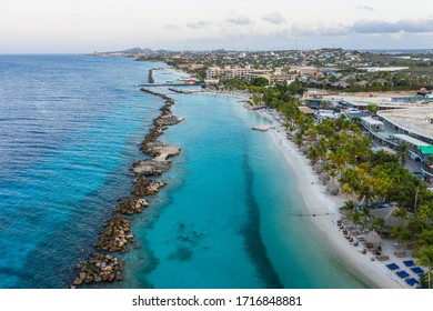 Aerial view of coast of Curacao in the Caribbean Sea with turquoise water, cliff, beach and beautiful coral reef around Mambo Beach
