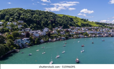 Aerial view of coastal town on estuary with moored boats in South Devon