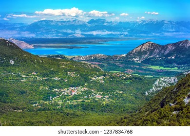 Aerial view of the coastal zone in front of the lake between the big mountains with a green forest, road and villages in the valley under the beautiful sky. Skadar Lake, Podgorica region, Montenegro.