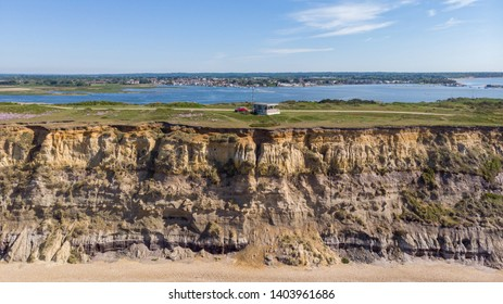 An aerial view of a coastguard tower on the top of a hill with eroded cliff along a sandy beach with an harbor in the background under a majestic blue sky and some white clouds