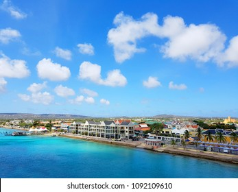aerial view of the coastline city of Kralendijk, capital of Bonaire, with colorful buildings and blue sea and sky.