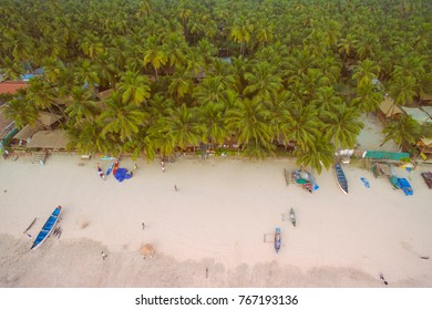 Aerial view of coastline of Indian ocean with tropical forest, water and fishing boats, Palolem beach, South Goa. Top photo from flying drone for your advertising text message or promotional content.