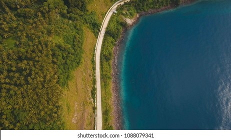 Aerial view coastline on tropical island Camiguin with road, sea, trees and palms.Road along the coast. Amazingly beautiful landscape of nature with hills, rain forest. Seascape: Ocean. Philippines