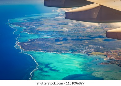 Aerial view of a coastline. Plane wing on the foreground. Mauritius