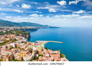 Aerial view of coastline Sorrento city and Gulf of Naples - popular tourist destination in Italy. Sunny summer day with blue sky, clear sea and green mountains of Sorrento  peninsula.