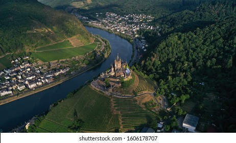 Aerial view of Cochem Castle on the hill near river surrounded by green vineyards, trees, fields, small houses, bridge. German flag waving on the top of tower. Summer. Germany historical landmarks.