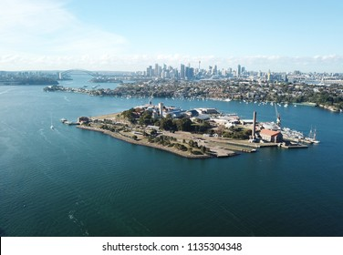 Aerial view of Cockatoo Island, Sydney CBD and Harbour Bridge with Sydney tower and financial district skyscrapers.