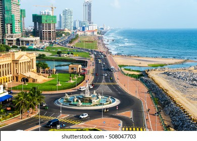 Aerial view of Colombo, Sri Lanka modern buildings with coastal promenade area. Car traffic during the day. Ocean waves