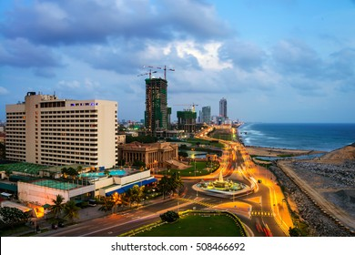 Aerial view of Colombo, Sri Lanka modern buildings with coastal promenade area. Car traffic during the night. Sunset sky and ocean waves