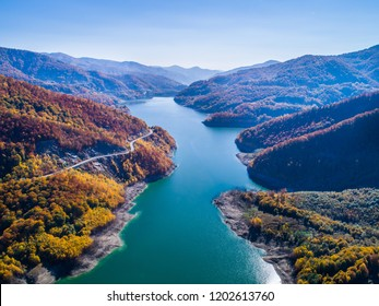 Aerial view of colorful forest trees and turquoise lake in the autumn season. Blue Lake and Autumn Forest Landscape Travel Concept. Fall forest and lake with colorful trees from above. October.