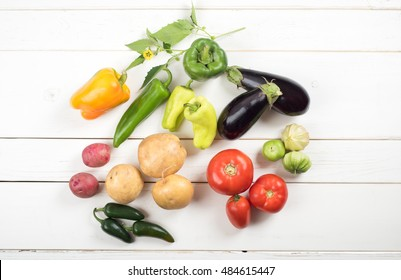 An Aerial View of a Colorful Group of Nightshade Vegetables fresh picked from the Garden on rustic white horizontal board background with room or space for copy, text, your words on side.