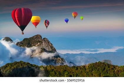 Aerial view colorful hot air balloons flying over with the mist at Doi Luang Chiang Dao with  morning mist in Chiang Mai, Thailand.
