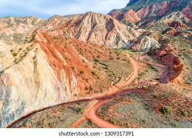 Aerial view of colorful rock formation and steep cliff along Onion Creek and dirt road in Moab area, Utah