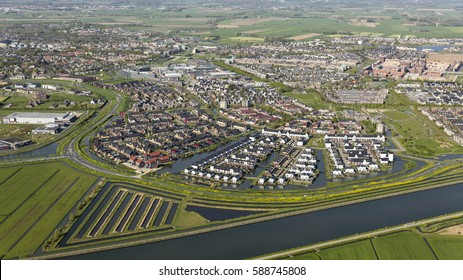 Aerial view of colourful new built houses and villa's in a residential area in Houten, province Utrecht, The Netherlands. In the front are the canal Amsterdam-Rijnkanaal and green fields.