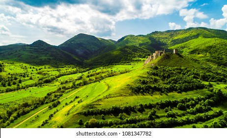 Aerial view of Coltesti Fortress in Transylvania, Romania on a sunny spring day with green hills around and beautiful blue sky with clouds