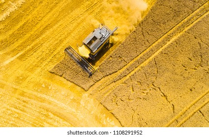 Aerial view of combine harvester on rapeseed field. Agriculture and biofuel production theme.