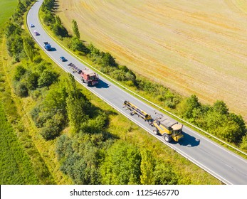 Aerial view of combine harvesters moving on the road towards next harvest. Traffic jam from drone view. Typical summer seasonal traffic situation.