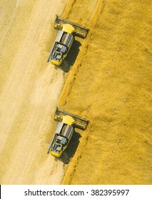 Aerial view of combine harvesters on wheat field. Industrial background on agricultural theme. Use drones to inspect of your business.