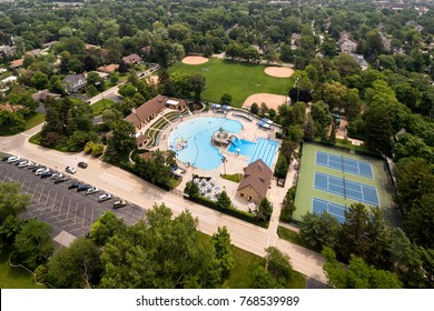 Aerial view of a community swimming pool in a suburban setting with tennis courts and baseball diamonds.