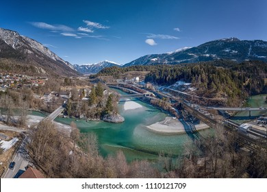Aerial view of the confluence of the Rhein river in Reichenau-Tamins Canton Graubünden Switzerland with turquoise water and white stone banks and mountains of the Swiss Alps in background