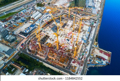 Aerial view of a Construction crane tower. Top view Crane and building working progress. Worker. Construction Site view by drone. Aerial top view a New buildings with a crane. Tower crane
