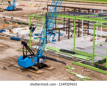 Aerial View of Construction Site with Blue Crane and Green Steel Frame Construction