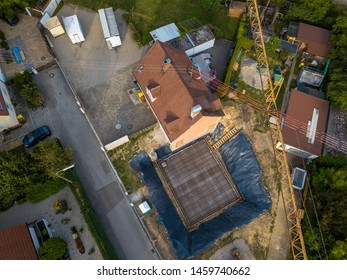 Aerial view of a construction site within a village in Germany. Looking straight down with a satellite image style, the houses look like a miniature village
