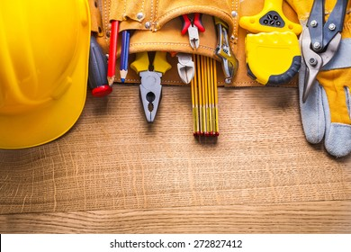 aerial view construction tools  in toolbelt hammer tapeline wrench nippers pliers cutter pencil screwdriver helmet on wooden board
