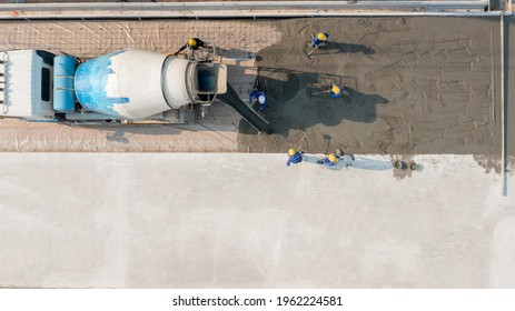 Aerial view a constuction worker pouring concrete road at construction site