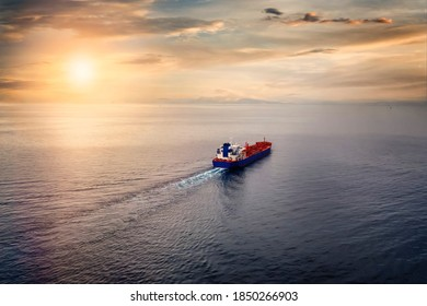Aerial view of a container cargo ship sailing over calm sea into the sunset