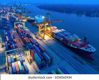 Aerial view of Containers yard in port congestion with ship vessels are loading and discharging operations of the transportation in international port.Shot from drone.