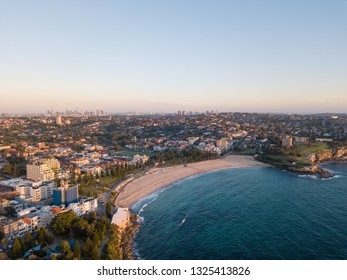 Aerial view of Coogee Beach with Sydney skyline at the distance.